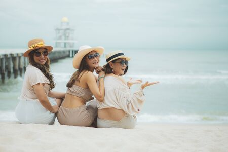 three asian woman sitting on vacation sea beach with happinessw emotion Stock fotó
