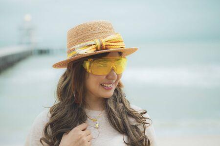 headshot of beautiful asian woman wearing yellow eye glasses standing at sea beach