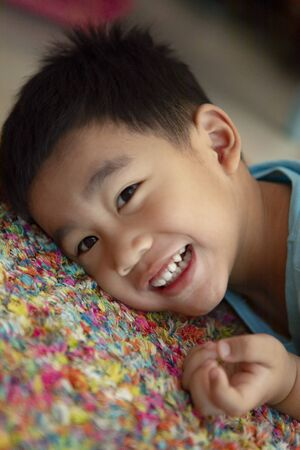 toothy smiling face of asian toddler lying on floor