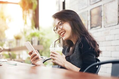 beautiful asian younger woman drinking cool green tea in bottle and looking on mobile phone screen with happiness face