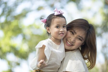 close up happiness face of asian mother and little daughter toothy smiling outdoor Stock fotó