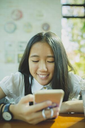 face of asian teenager looking to smartphone screen and toothy smiling with happiness