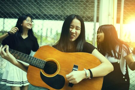 group of asian teenager standing outdoor plying spanish guitar and dancing with happiness emotion Stock fotó