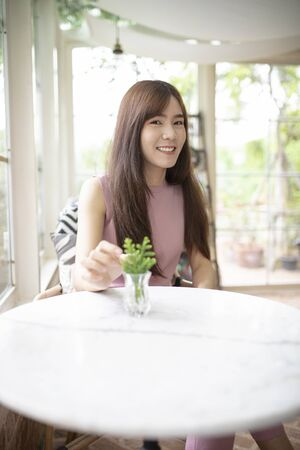 face of beautiful asian younger woman smiling with happiness in living room