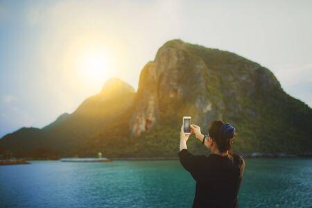 Frau, die mit dem Smartphone ein Foto von Sonnenaufgang und Meeresküste macht
