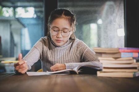 asian teenager doing school home work in library room