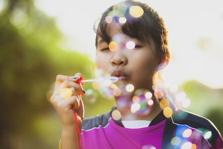 asian teenager relaxing with soup bubble against beautiful sun light
