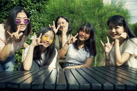 group of asian teen and younger woman hand sign i love you with happiness smiling face Imagens