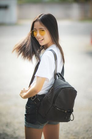 cheerful asian teenager with fashion backpack standing outdoor