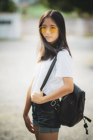 beautiful asian teenager with fashion backpack standing outdoor