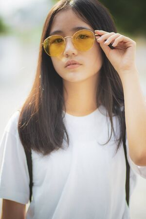 cheerful asian teenager wearing sunglasses with relaxing outdoor