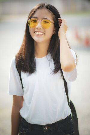 toothy smiling face of asian teenager standing outdoor