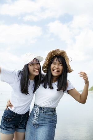 two cheerful asian teenager happiness on vacation sea beach