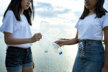 two asian teenager holding one way plastic bottle used on hand against ocean floor background