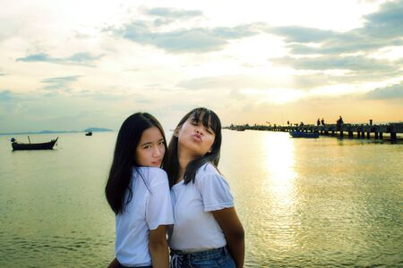 two asian teenager relaxing with happiness on summer vacation sea beach