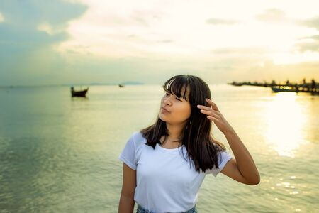 asian teenager relaxing on summer vacation sea beach against sunset sky Stock fotó
