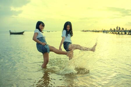 two asian teenager relaxing and playing ons summer vacation sea beach