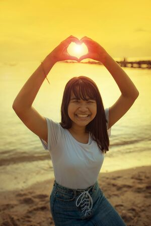 asian teenager sign heart shape by hand with beautiful sunset sky background
