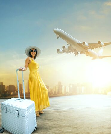 beautiful woman and traveling luggage standing in airport terminal with passenger plane flying over sky Stock fotó