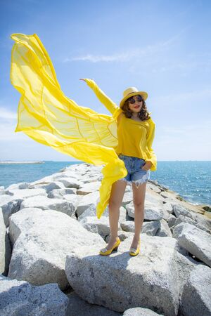 beautiful asian woman wearing yellow clothes standing on sea beach against midday sun light Archivio Fotografico