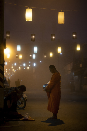 maehongsorn thailand - jan22,2017 : thai buddhist monk receiving food from people on foggy street in maehongsorn northern of thailand