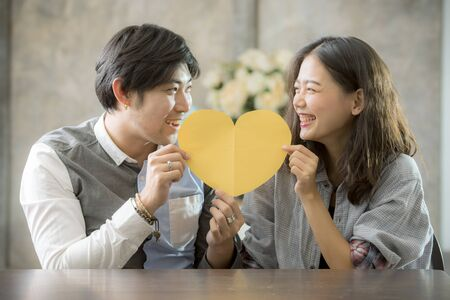 couples of asian man and woman holding heart shape paper cut with happiness emotion ,people love conceptual Foto de archivo