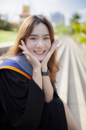 happiness smiling face of asian younger woman wearing university gruation suit