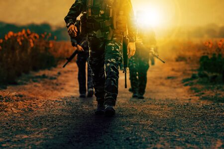 soldier with long rifle gun walking on dirt battlefield