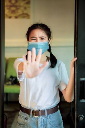 asian teenager wearing protection mask standing with hand sign do not closer 版權商用圖片