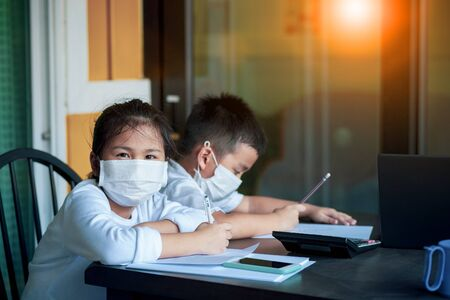 asian children wearing protection mask writing homework in home living room while covid-19 virus infected in bangkok thailand