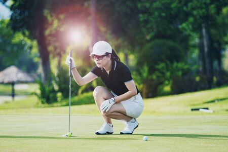 woman approach for looking golf put shot on green golf hole