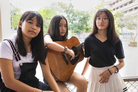 three asian teenager playing guitar like a band