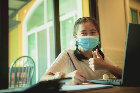 asian teenager wearing protection mask working on computer laptop in home living room while covid-19 infected in south east asia