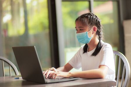 asian teenager sitting in homing living room and  typing on computer laptop