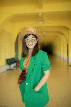 toothy smiling face of asian woman wearing green suit standing against yellow background