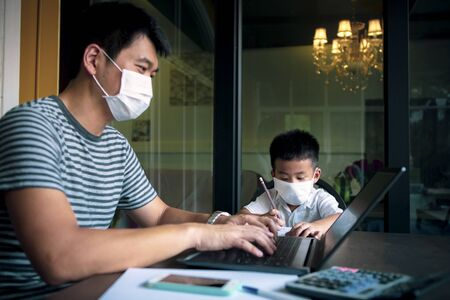 quarantine asian man and children wearing protection mask working on computer at home while covid-19 virus infected global Stock fotó