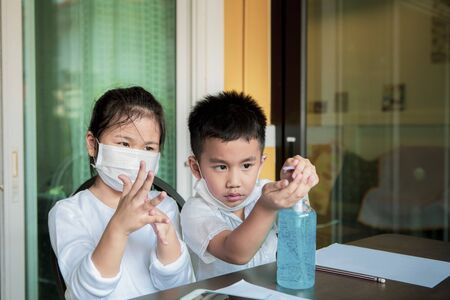 children wearing protection mask with alcohol gel on working table