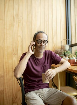 asian man talking on smart phone with coffee cup in left hand