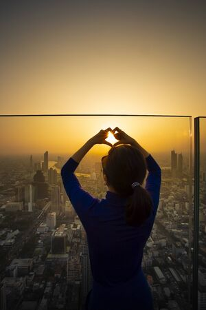 woman standing on high building roof and making heart shape finger cover beautiful sunset sky Stock fotó