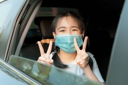 asian teenager wearing protection mask rising victory sign in passenger car seat