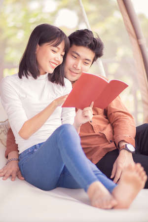 couples of younger asian woman and man relaxing and reading a book, Stock fotó