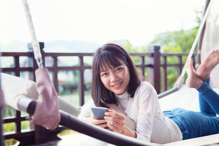 beautiful asian younger woman lying with smartphone and toothy smiling face Stock fotó