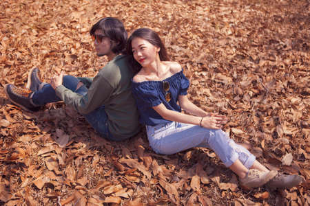 young asian couple sitting on dry leaves ground