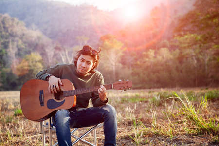 asian younger man and acoustic guitar sitting on open field against beautiful sun light Stock fotó