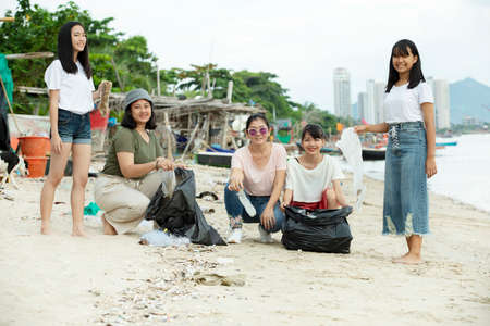 group of asian volunteer make a cleaning sea beach out of a plastic litter