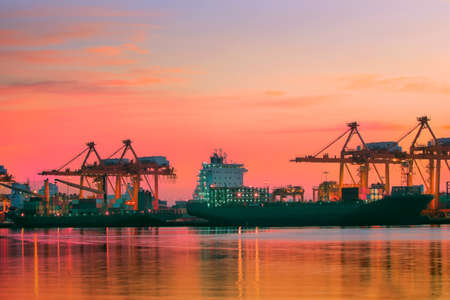 container ship at logistic port against beautiful sunset sky