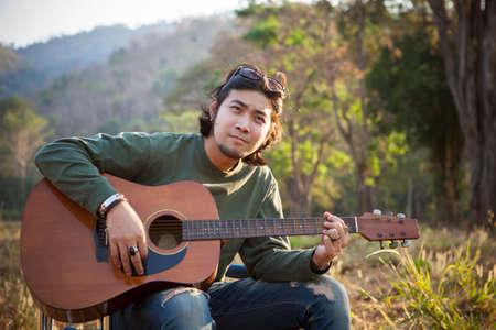 asian man playing acoustic guitar in natural field Stock fotó