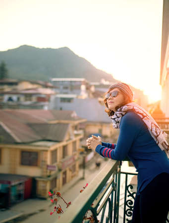 woman standing on building terrace against beautiful morning sun light