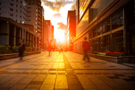 people walking in wall street against beautiful light of sunset sky