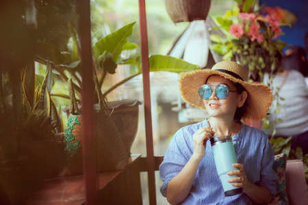 woman relaxing with cool drink bottlin in hand